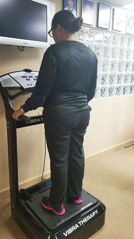 A patient using the vibra therapy machine at Spine & Sports Therapy in Saint Petersburg Florida
